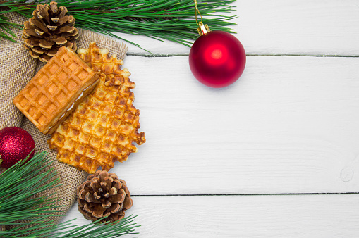 Branch christmas tree with red ball and waffles on burlap on white wooden vintage background