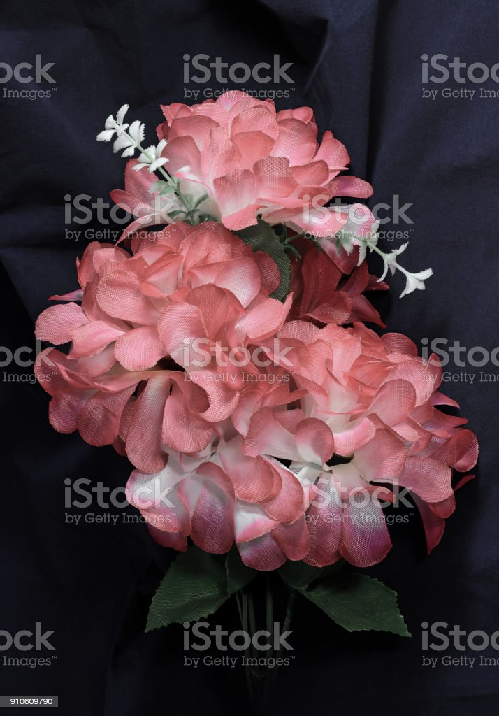 branch faded artificial flowers stock photo