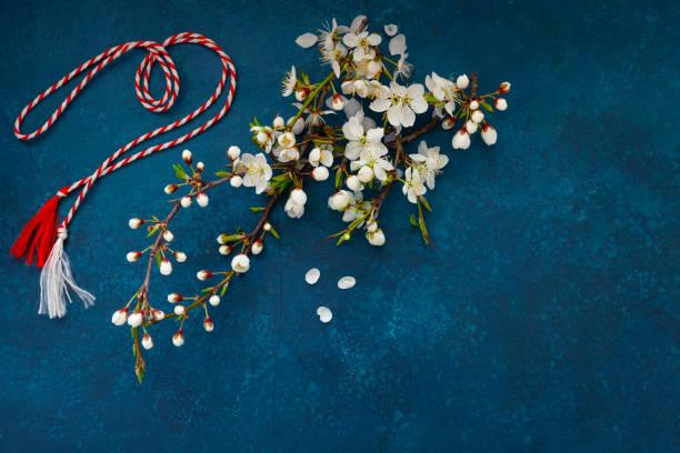 Filial da árvore de cereja de florescindo com o martisor vermelho e branco do cabo - símbolo tradicional do primeiro dia de mola no fundo azul clássico - foto de acervo