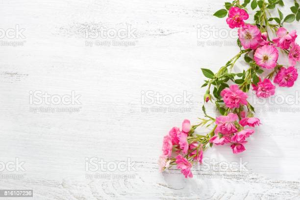 Photo of Branch of  small pink roses on a  shabby wooden table. flat lay