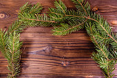 Christmas tree branches on colored rustic wooden background. Winter holidays