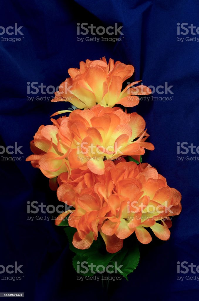 branch orange artificial flowers stock photo