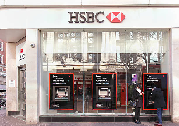 HSBC branch London, United Kingdom - February 08, 2015: HSBC bank branch with glass wall and people on Oxford Street in London using ATM machines hsbc stock pictures, royalty-free photos & images
