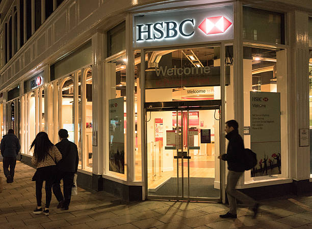 HSBC Branch Edinburgh, UK - January 25, 2016: Pedestrians on the pavement at night, passing a branch of HSBC Bank, located on Princes Street in central Edinburgh. hsbc stock pictures, royalty-free photos & images