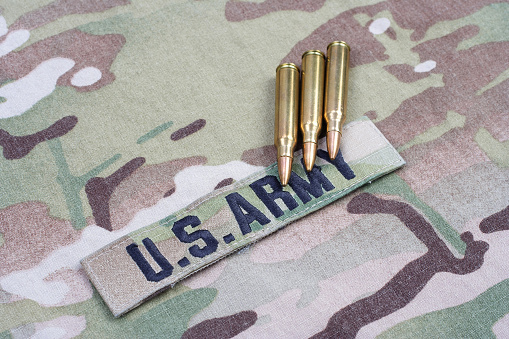 istock US ARMY branch tape and 5.56 mm rounds on camouflage uniform 1190926094