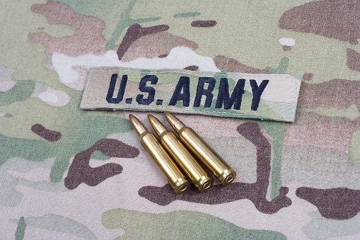 istock US ARMY branch tape and 5.56 mm rounds on camouflage uniform 1190926096