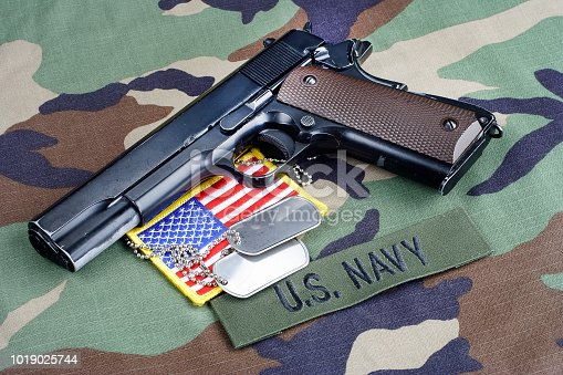 istock US NAVY branch tape, M1911 handgun with dog tags on woodland camouflage uniform 1019025744