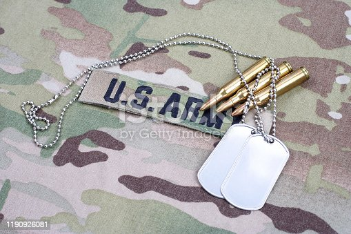 istock US ARMY branch tape with dog tag and 5.56 mm rounds on camouflage uniform 1190926081
