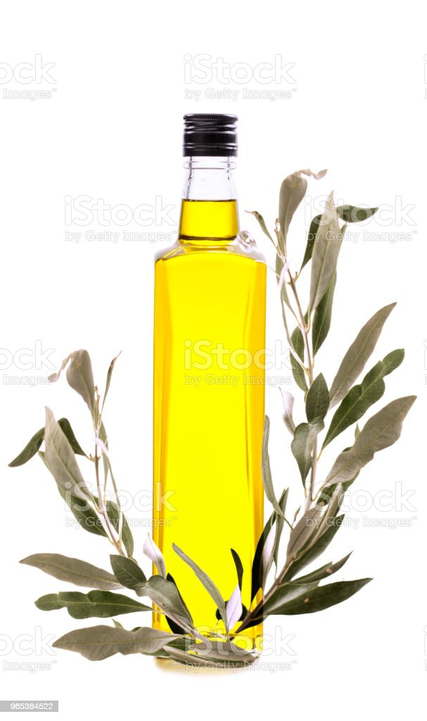 Branch with green olives and a bottle of olive oil isolated on white zbiór zdjęć royalty-free