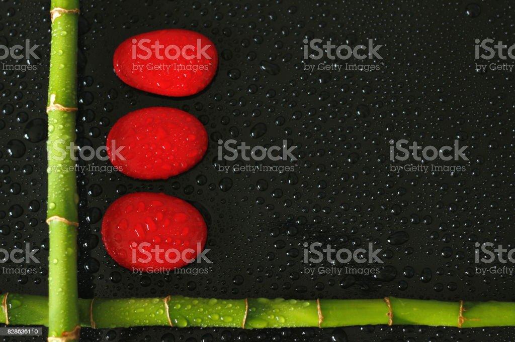 branche de bambou en angle droit sur le cote en bas à gauche avec des galets rouge mouillé de gouttes d'eau sur fond noir stock photo