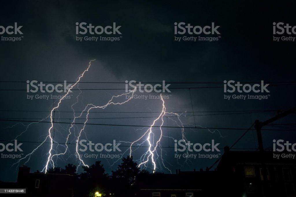 Branched lightning bolts over the city of Vlaardingen near Rotterdam, Netherlands. stock photo