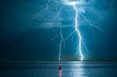 Violent lightning bolts strike the water off the Dutch coast.
