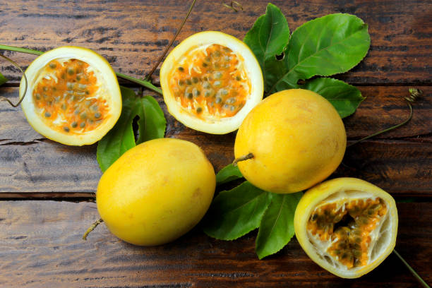 branches and leaves with yellow passion fruit and passion fruit cut in half isolated on wooden table. top view closeup - passiflora foto e immagini stock