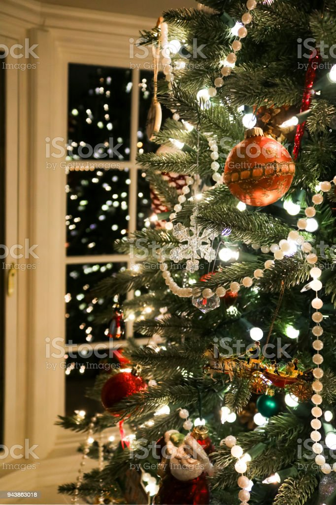 branches of old fashioned christmas tree trimmed with pearls and an assortment of beautiful ornaments reflected