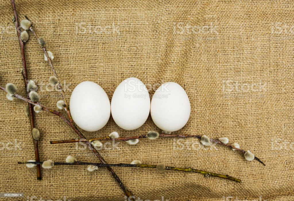 Branches of willows and Easter eggs on a rustic background. stock photo