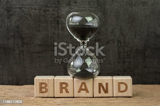 istock Brand communication for product and service advertising, Hourglass or sandglass on wooden cube block with alphabet building the word Brand on wood table, dark black background 1166212803