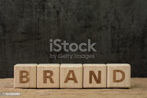 istock Brand communication for product and service advertising, wooden cube block with alphabet building the word Brand on wood table, dark black background 1164095983