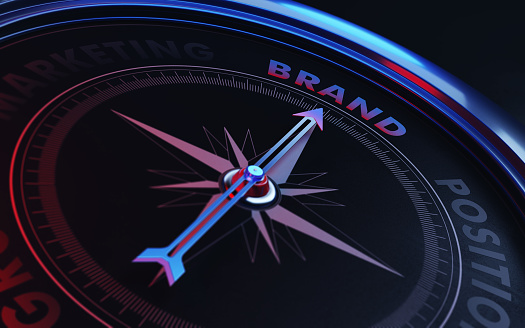 Arrow of a compass is pointing brand text on the compass. Arrow, brand text and the frame of compass are metallic blue in color. Red light illuminating compass is creating a sense of tension. Black backgound. Horizontal composition with copy space. Brand concept.
