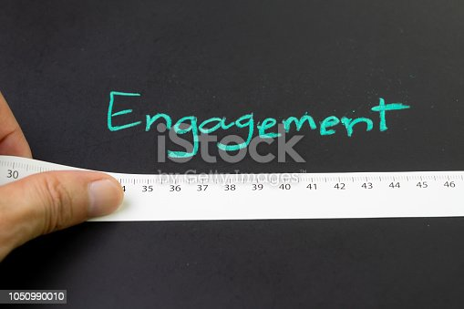 istock Brand engagement with measurable metrics in online and offline marketing campaign concept, hand holding measuring tape with centimeter with handwriting chalk word Engagement on blackboard 1050990010
