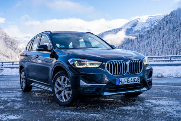 Brand new black BMW X1 SUV 2020 parked in Switzerland Brand new black BMW X1 SUV 2020 parked in Switzerland by the highway with beautiful winter mountains in the background. bmw stock pictures, royalty-free photos & images