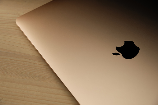Brand new gold macbook air (2020) on a wooden table.