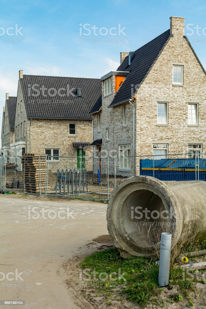 Brand new houses creme stone  strip houses with sewage pipe stock photo