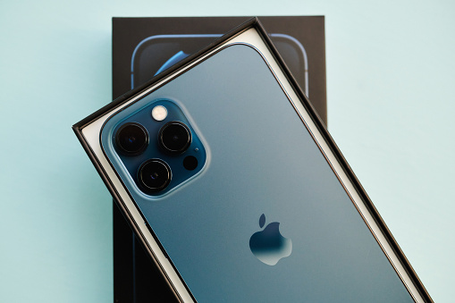 17 November 2020 - Peyton, Colorado, USA: A studio shot of a brand new iPhone 12 Pro Max in Pacific Blue in the box it was shipped in. Shot on a pale blue surface