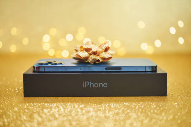 Brand new iPhone 12 Pro Max in Pacific Blue with Gold Bow in Studio Setting stock photo