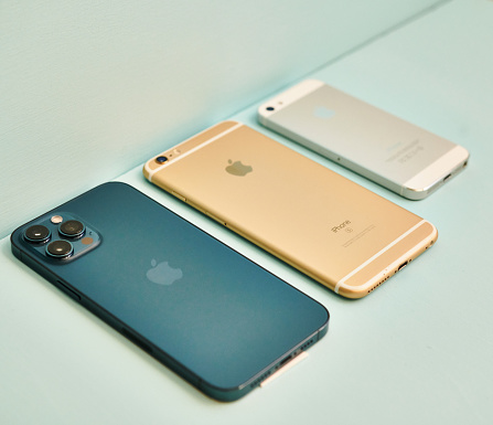 17 November 2020 - Peyton, Colorado, USA: A studio shot of a brand new iPhone 12 Pro Max in Pacific Blue with a gold iPhone 6S Plus and a silver iPhone 5 next to it. Shot on a pale blue surface