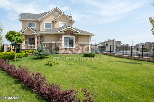 697393252 istock photo Brand new suburban house in sunny summer afternoon 184332617