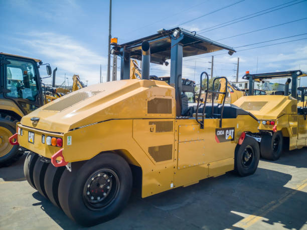 Brand new yellow Caterpillar CW34 pneumatic roller Johannesburg, South Africa - November, 2018: Brand new Caterpillar CW34 pneumatic roller waiting in lot to be shipped to a customer compactor stock pictures, royalty-free photos & images