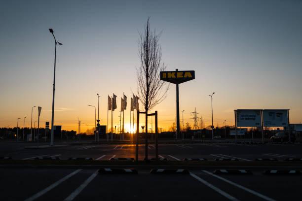 riga, latvia-april 3, 2019: ikea markenzeichen bei dunklem abend und wind-blauer himmel im hintergrund - ikea vorzimmer stock-fotos und bilder
