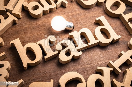 BRAND word in scattered wood letters on the table with glowing light bulb