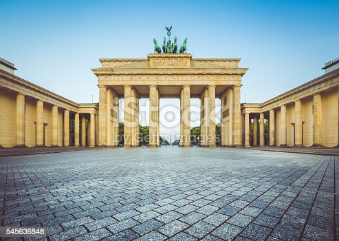 Famous Brandenburger Tor (Brandenburg Gate), one of the best-known landmarks and national symbols of Germany, in beautiful golden morning light at sunrise with retro vintage Instagram style pastel toned filter effect, Berlin, Germany