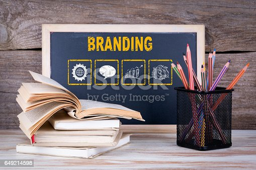657955676 istock photo Branding concept. Stack of books, chalk blackboard with pencils on the wooden table. 649214598