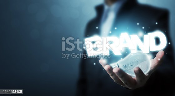1027533352 istock photo Branding idea concept. Businessman hand holding light bulb and word BRAND with bokeh background 1144453405