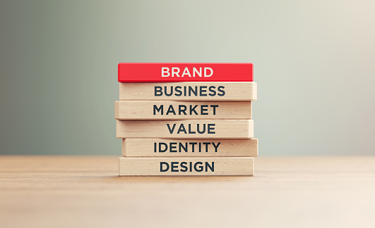 Branding related words written woodblocks sitting on wood surface in front of a defocused background. Brand concept.