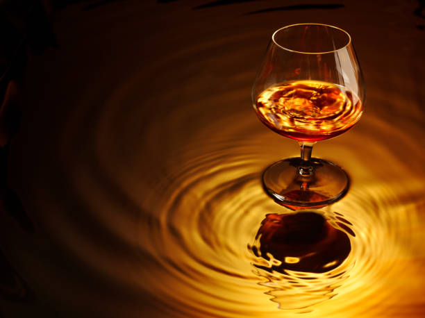 Brandy and Glass Glass of brandy sitting on water. Copy spaceClick on the link below to see more of my drink images. brandy stock pictures, royalty-free photos & images