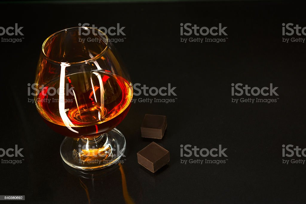 Brandy glass and chocolate on black background stock photo
