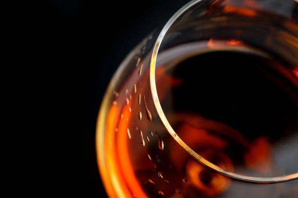 brandy in  glass snifter of  brandy in  elegant  glass.  black background calvados stock pictures, royalty-free photos & images