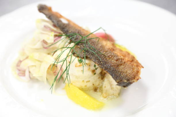 Branzino with crispy skin cracker, orange, beet, fennel salad. stock photo
