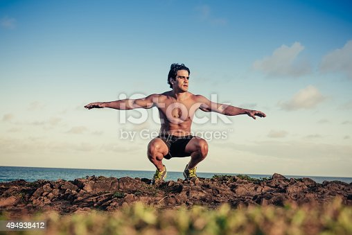 istock brasilian bare-chested sportsman spreading arms for exercising at beach 494938412