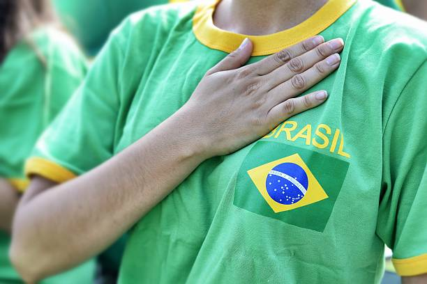 brasilian fan putting hand on hearth during the national anthem - national anthem stock photos and pictures