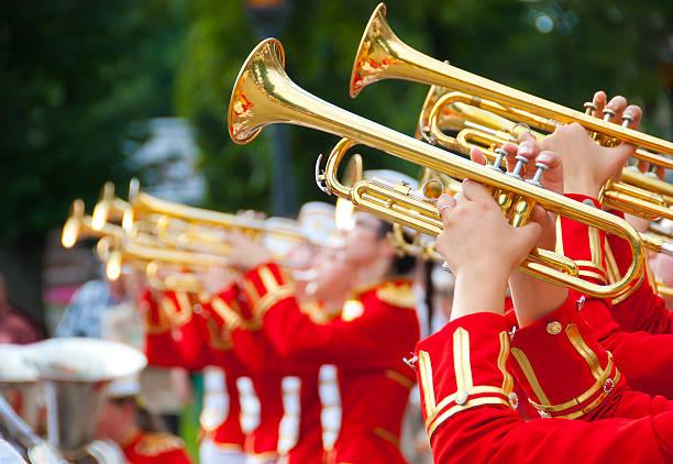 brass band of girls playing their instruments together - geçit töreni stok fotoğraflar ve resimler
