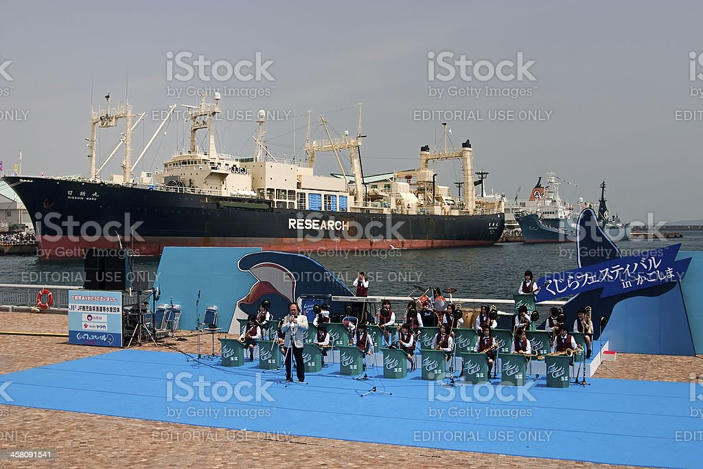 Brass band performs with Japanese whaling ship Nisshin Maru background stock photo