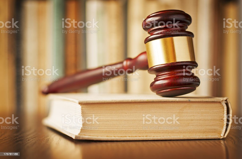 A brass banded wooden judges gavel on a book royalty-free stock photo