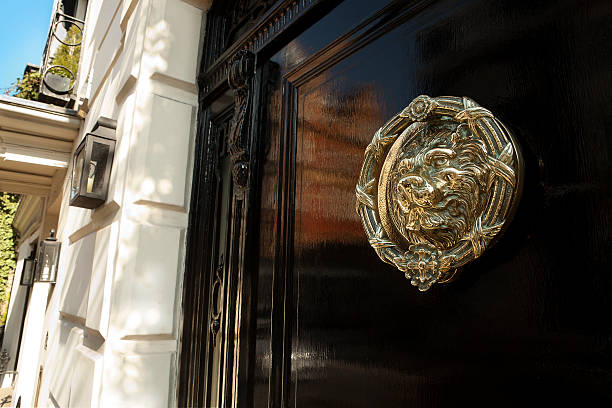 Brass door knocker, Mayfair, London XXXL Black gloss door with brass door knocker of a lion. Lovely spring time sunshine and reflection in the gloss black door. Central Mayfair, London mayfair stock pictures, royalty-free photos & images
