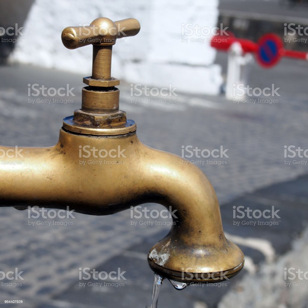 brass dripping tap or faucet in a public street stock photo