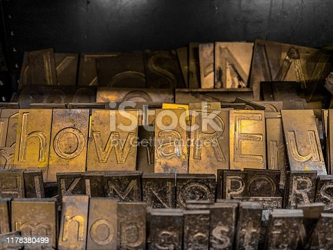Lots of different Brass metal letter sets with lots of brass coloured letters and the word how are u in the centre