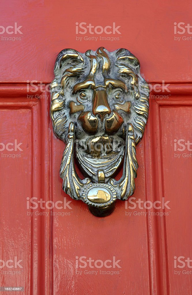 Brass lions head knocker on a red door royalty-free stock photo